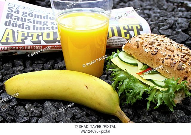 Breakfast including sandwich, orange juice and coffee and a newspaper to read