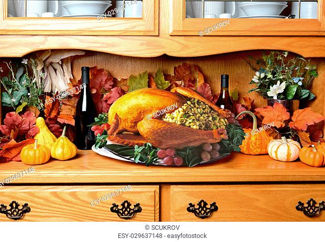 Thanksgiving turkey on a sideboard. The still life has fall leaves, pumpkins and decorative gourds wine bottles. The turkey is stuffed with garnish surrounding...