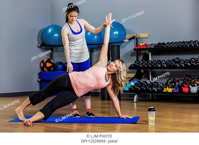 A middle-aged women doing a side plank yoga exercise at the gym with her personal trainer giving assistance; Spruce Grove, Alberta, Canada