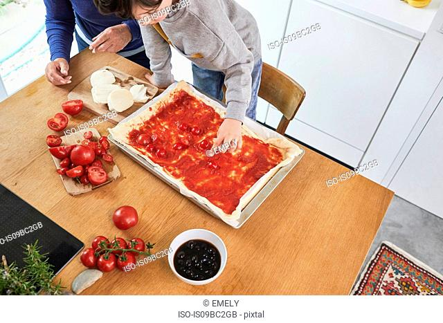 Grandmother and grandson making pizza in kitchen, elevated view