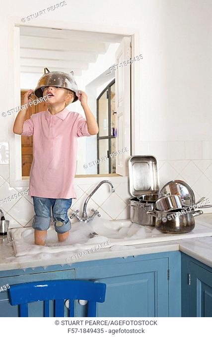 Four year old boy playing in the kitchen sink