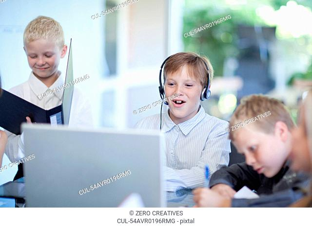 Boys playing businessmen at desk