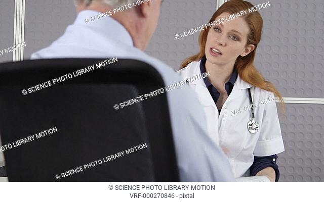 MODEL RELEASED. Young female doctor listening to senior male patient