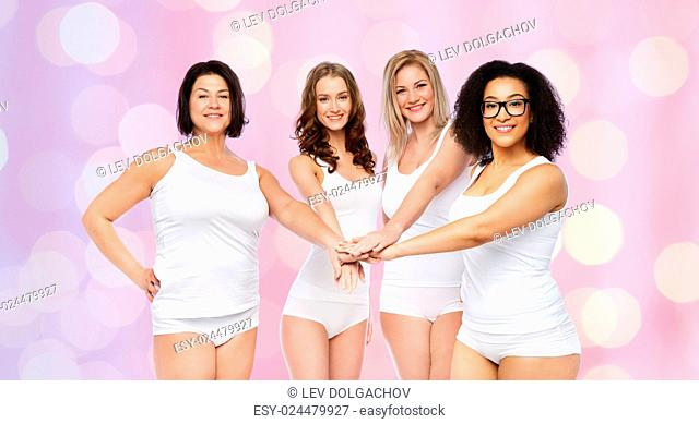 gesture, friendship, beauty, body positive and people concept - group of happy different women in white underwear holding hands together on top over rose quartz...
