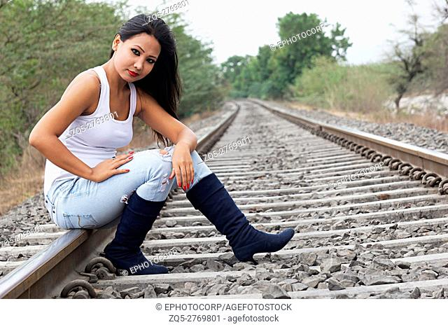 Young woman with jeans and boots sitting on railway track, Pune, Maharashtra