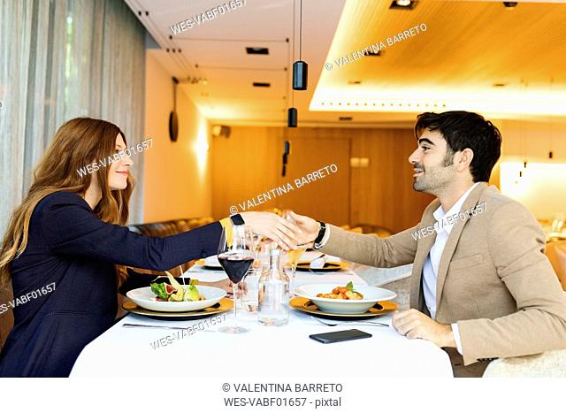 Smiling man and woman shaking hands in a restaurant