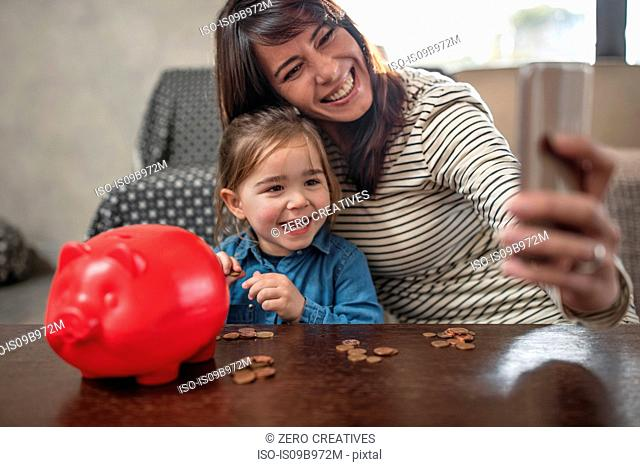 Mature woman taking smartphone selfie with daughter and piggy bank on coffee table