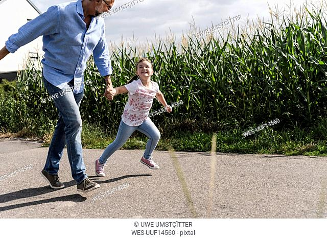 Mature man and little girl running on street, laughing