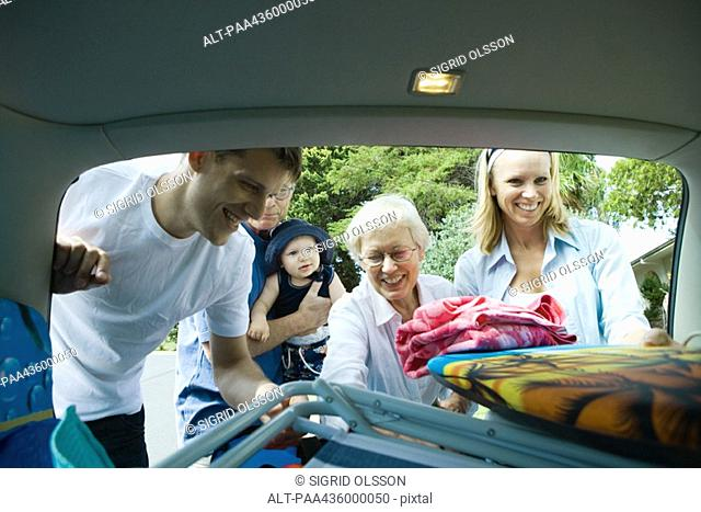 Family unloading beach material out of trunk of car