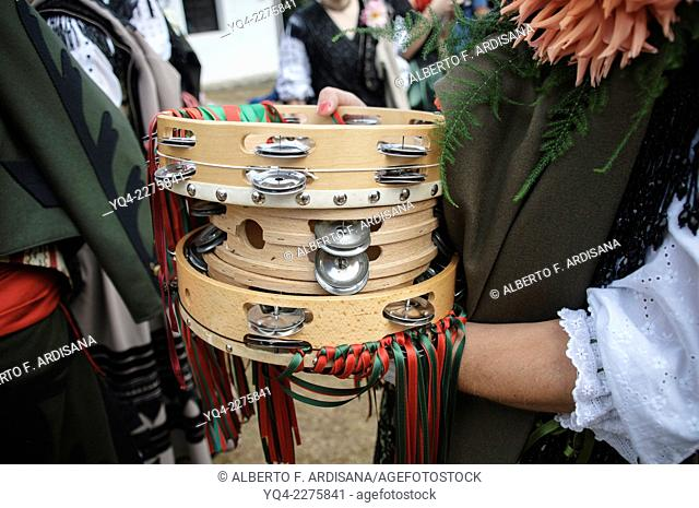 A woman dressed in traditional costume, holds some tambourines in hand during the procession of Lledías. Llanes, Asturias, Spain
