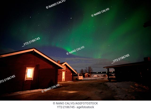 Aurora Borealis (Northern Lights) over VisitInari wood cabins in Lake Inari, Lapland, Finland