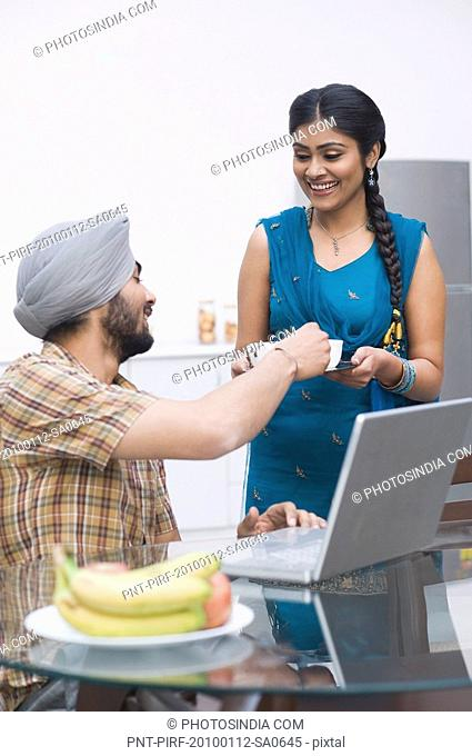 Woman serving tea to her husband working on a laptop