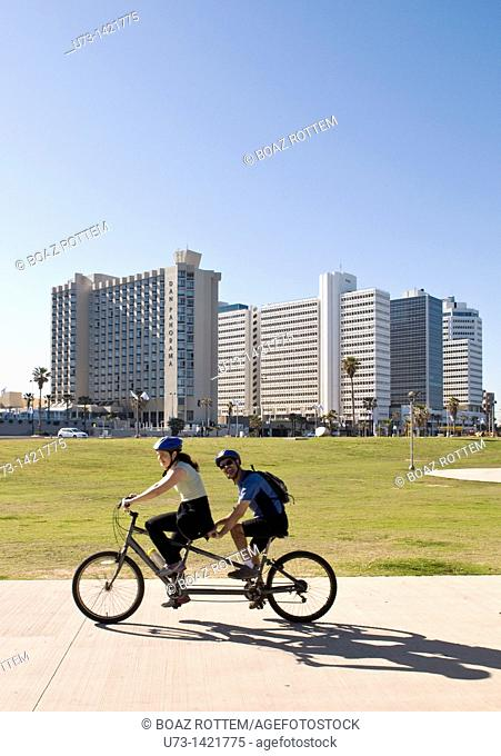 An Israeli couple riding a tandem bicycle on the promenade in Tel Aviv