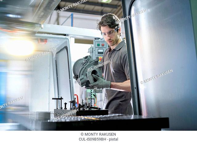 Apprentice engineer preparing component in precision casting factory