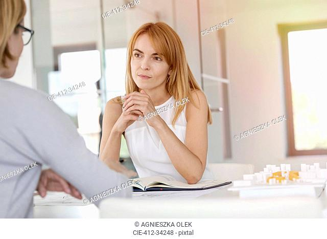 Attentive businesswoman listening to colleague in meeting