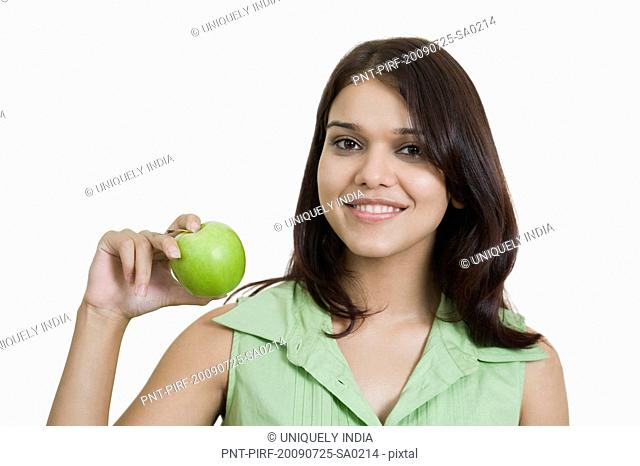 Portrait of a woman holding a green apple and smiling