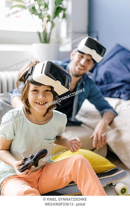 Portrait of happy boy and father wearing VR glasses playing video game at home