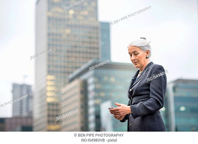 Businesswoman using mobile phone, Canary Wharf, London, UK