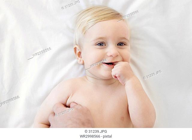 High angle view of smiling baby boy lying on a bed