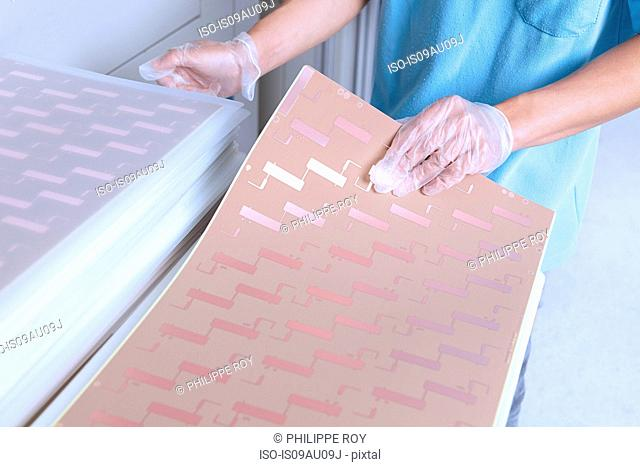 High angle view of young man wearing latex gloves sorting sheets of flexible circuits