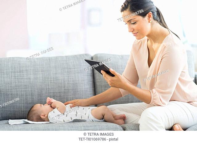 Mother playing with baby boy (2-5 months) and using digital tablet