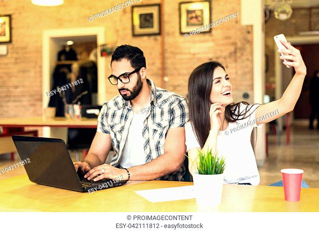 Beautiful couple of colleagues, bearded man and brunette girl taking selfie with smartphone in modern coworking office