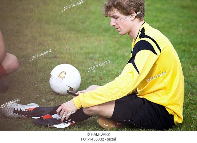 Young soccer player holding mobile phone while sitting on field