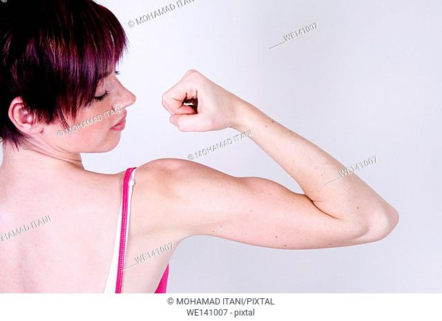 young woman flexing her bicep muscle
