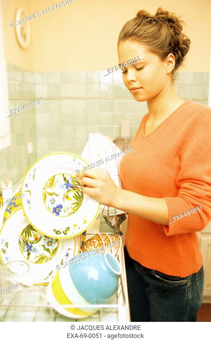 Woman drying dishes in dish drain