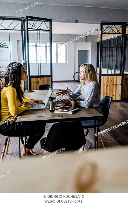 Two young businesswomen talking at conference table in loft office