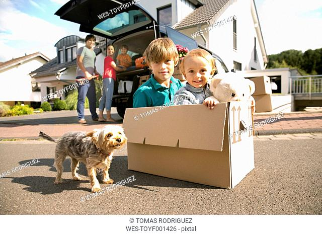 Two brothers with dog inside cardboard box on the road with family in background