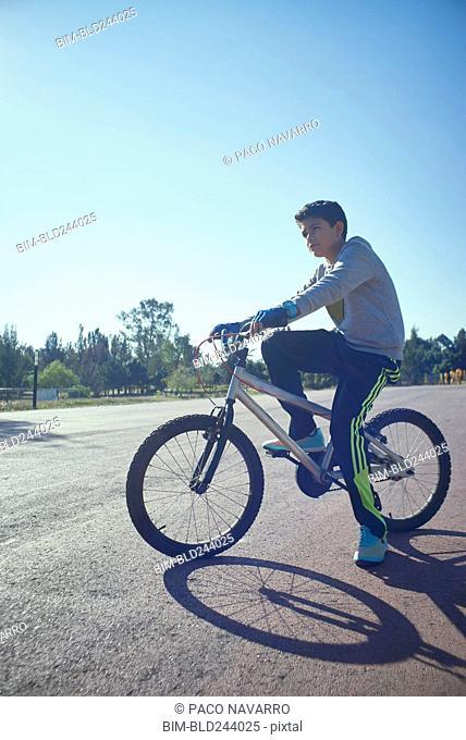 Serious Hispanic boy on bicycle