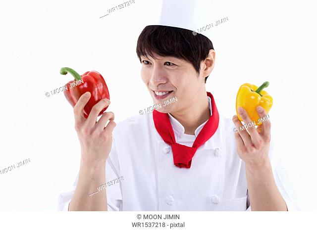 a man wearing a chefs uniform posing with bell peppers