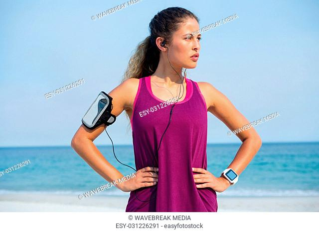 Thoughtful young woman standing with hands on hip at beach