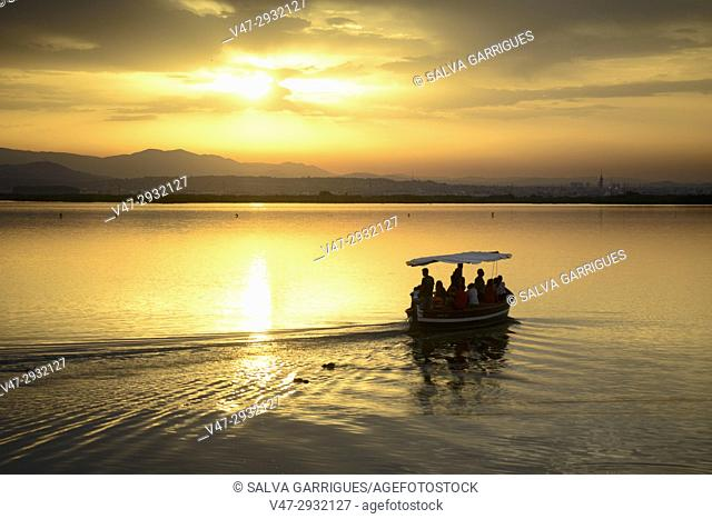 Tourists strolling by boat in the Albufera at sunset, Valencia, Spain