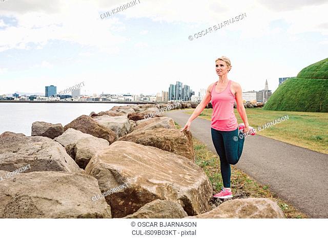 Female runner stretching leg waterfront, Reykjavik, Iceland