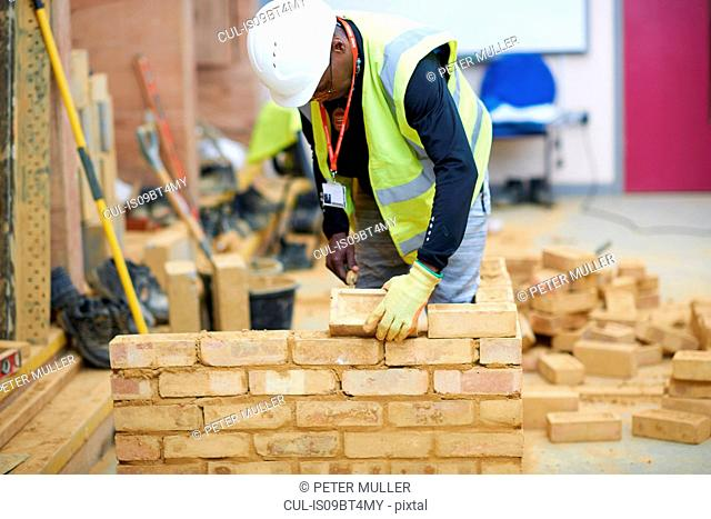 Lecturer building brick wall in classroom