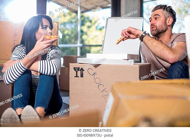 Couple in new home, surrounded by boxes, eating pizza