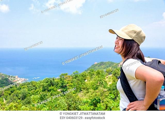 Women tourist with a backpack wear cap standing happily look at beautiful nature landscape blue sea and sky from high scenic viewpoint at Koh Tao in Surat Thani