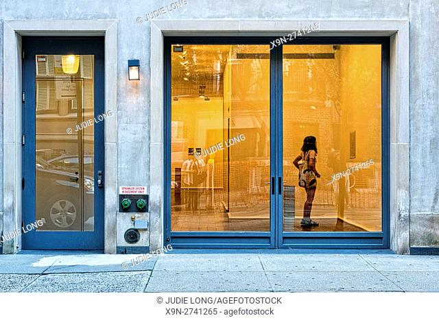 Looking Through a Small Art Gallery Window at an Unidentifiable Woman Admiring a Painting. New York City