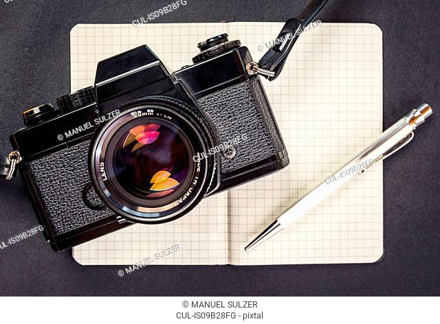 Overhead view of retro camera, notebook and pen