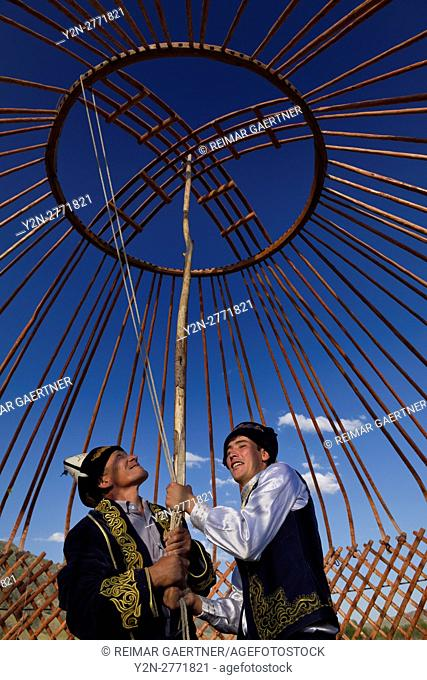 Kazakh men supporting wood frame roof of Yurt during assembly in Saty Kazakhstan