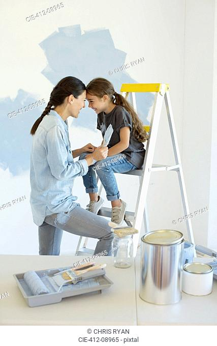 Mother and daughter painting wall blue