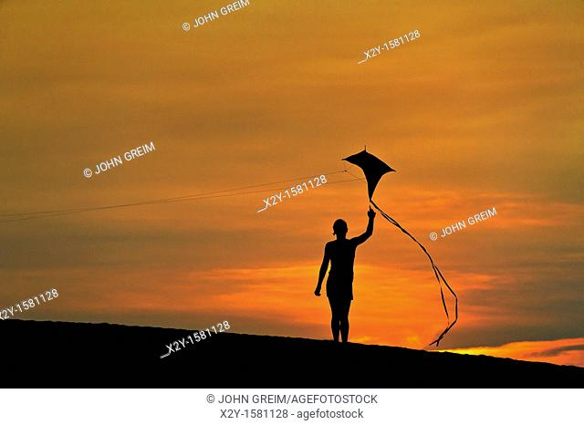 Silhouette of a child flying a kite