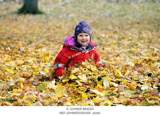 Portrait of girl playing with autumn leaves in park