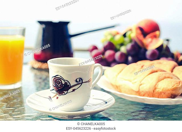 Healthy breakfast with a cup of coffee and plate of delicate and lush croissant in the foreground, Turkish coffeepot, glass of orange juice