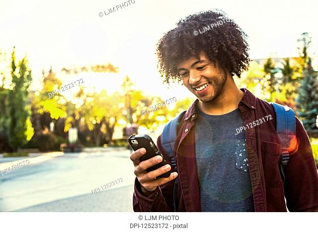 A young male African American student stands using his smart phone on a university campus; Edmonton, Alberta, Canada