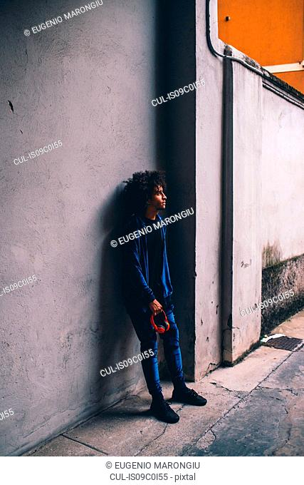 Young man waiting in front of concrete wall