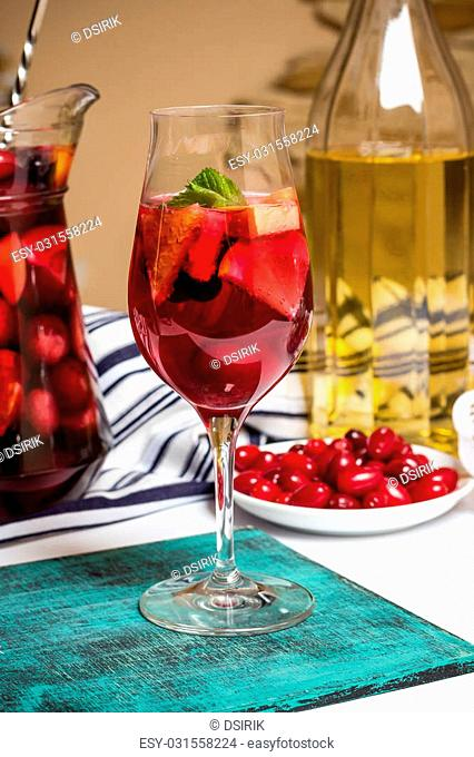 Summer home wine with fruits, sangria cocktail, in glass and jar, fresh dogwood berries plate, bright blue background, food photo