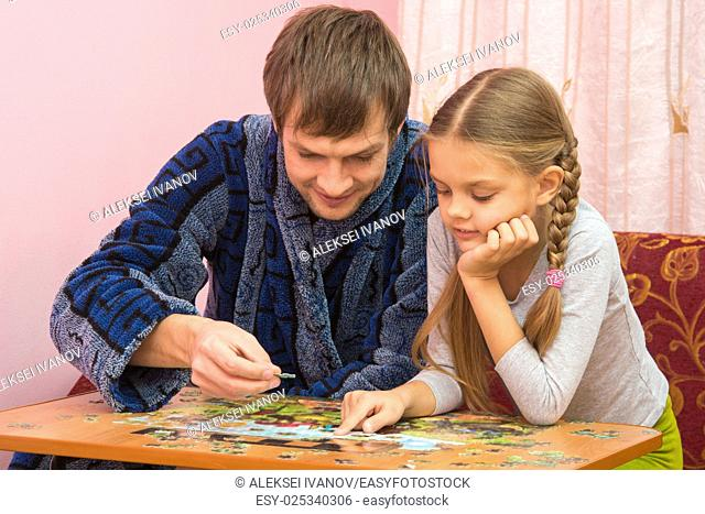 Dad and daughter enthusiastically collect picture of puzzles
